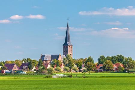 Petit village hollandais avec l'église dans la province de la Frise