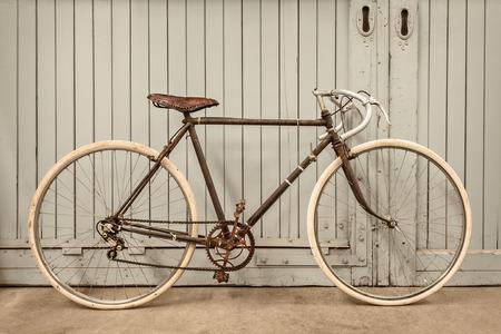 木製のドアの古い工場でヴィンテージレース錆びた自転車駐車 写真素材