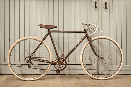 old school bike: Vintage rusted racing bicycle parked in an old factory with wooden doors Stock Photo