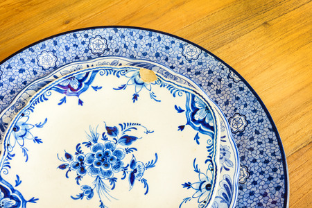 Genuine antique dinner plates from Delft on a wooden table photo