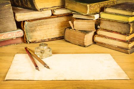 Imagen en tonos sepia de plumas estilográficas vintage con papel en blanco delante de libros antiguos sobre una mesa