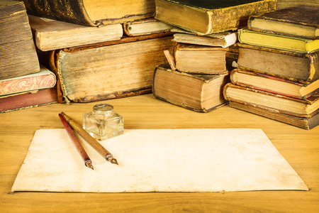 Sepia toned image of vintage fountain pens with blank paper in front of old books on a table