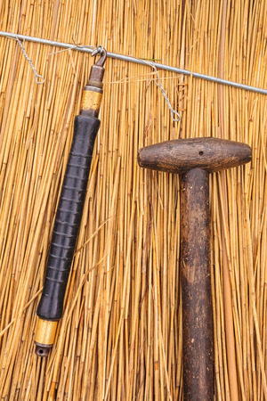 thatched house: Traditional thatch tools in front of a newly thatched roof