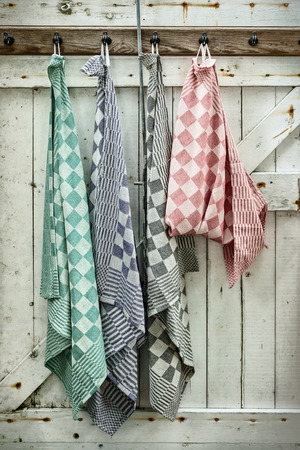 Retro styled image of hanging dish cloths on an old wooden door Standard-Bild