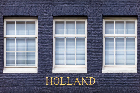 dutch canal house: Windows of an Amsterdam canal house with the bronze letters \Holland\ beneath it Stock Photo