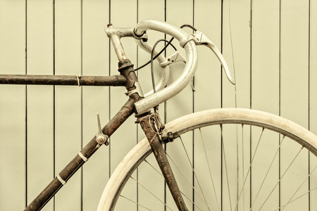 old school bike: Retro styled image of a vintage rusted racing bicycle in front of a wooden wall Stock Photo