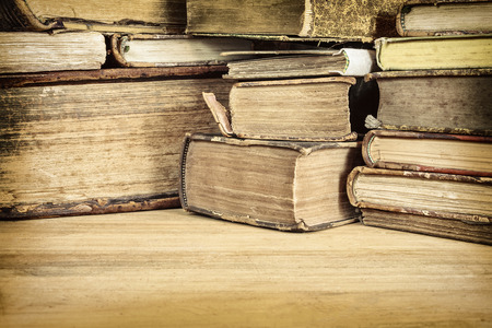 Sepia toned image of ancient books on a wooden table