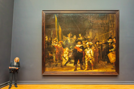 AMSTERDAM, THE NETHERLANDS - MARCH 12, 2015: View at the famous painting The Night Watch (1642) by Rembrandt van Rijn at the Rijksmuseum in Amsterdam, The Netherlands. It is prominently displayed as the best known painting in its collection. The Night Wat
