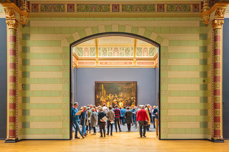 AMSTERDAM, THE NETHERLANDS - MARCH 12, 2015: Visitors looking at the famous 1642 painting The Night Watch by Rembrandt van Rijn at the Rijksmuseum in Amsterdam, The Netherlands
