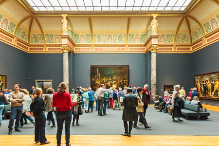 famous paintings: AMSTERDAM, THE NETHERLANDS - MARCH 12, 2015: Visitors looking at the famous 1642 painting The Night Watch by Rembrandt van Rijn at the Rijksmuseum in Amsterdam, The Netherlands