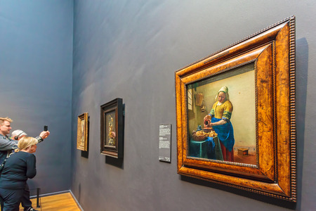 rembrandt: AMSTERDAM, THE NETHERLANDS - MARCH 12, 2015: Oil Painting of The Milkmaid by Johannes Vermeer from 1658 in the famous Rijksmuseum in Amsterdam at the museumplein, The Netherlands