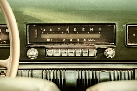 Imagen de una radio de coche viejo estilo retro dentro de un coche clásico verde Foto de archivo