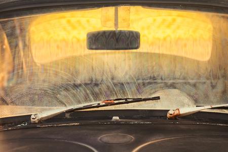 錆びたスクリーン ワイパーを汚れた古い黒い車のフロント ウィンドウ