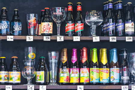 ANTWERP, BELGIUM - April 23, 2015: Different brands of Belgian beer bottles and glasses in a liquor store in Antwerp, Belgium