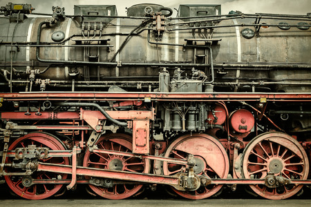 Retro styled side view of an old rusted steam locomotive photo