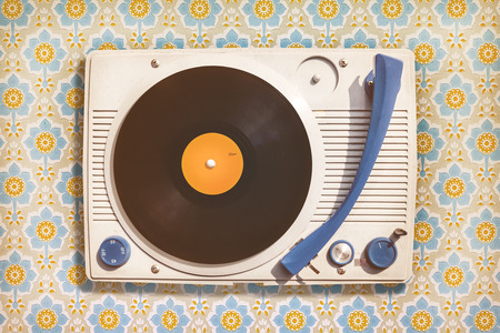 Retro styled image of an old record player on top of flower wallpaper Standard-Bild