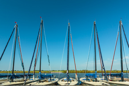 Row of small Dutch sailing boats used for sailing lessons in Friesland Stock Photo