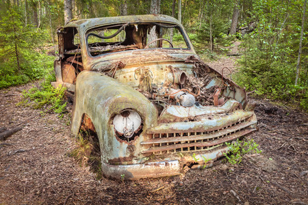 Old rusted and weathered scrap car in a forest