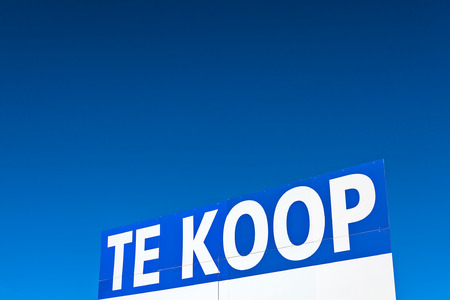 Large real estate sign with the Dutch text 'for sale' in front of a clear blue sky