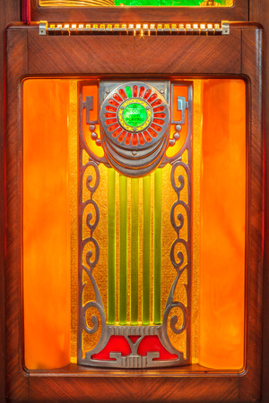 oldie: Close up of a vintage wooden jukebox with neon lights