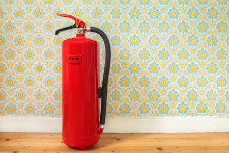 Fire extinguisher on an old wooden floor in front of retro flower wallpaper Stockfoto