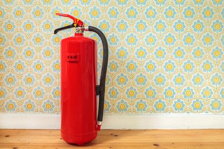 incendio casa: Extintor en un viejo piso de madera delante de papel tapiz de flores retro