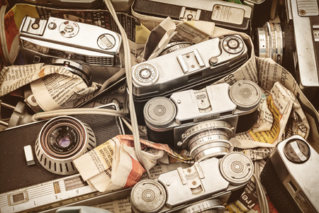 weathered: DOESBURG, THE NETHERLANDS - AUGUST 23, 2015: Retro styled image of old photo cameras packed in newspapers on a flee market in Doesburg, The Netherlands