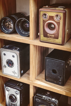 flee: DOESBURG, THE NETHERLANDS - AUGUST 23, 2015: Sepia toned image of old box cameras and a binocular on a flee market in Doesburg, The Netherlands Editorial