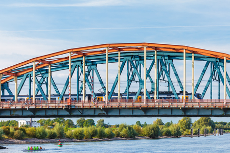 ijssel: ZUTPHEN, NETHERLANDS - SEPTEMBER 28, 2015: Cyclists and train crossing the IJssel bridge during rush hour in Zutphen, The Netherlands