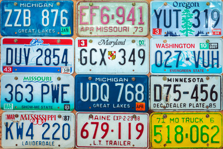 DREMPT, THE NETHERLANDS - OCTOBER 1, 2015: Vintage car license plates on a wall in Drempt, The Netherlands. In the U.S. each state issues its own car number plates.