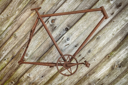 weathered: Rusted vintage bicycle frame hanging on an old wooden wall Stock Photo