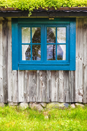 Typical ancient wooden farmhouse with blue window and grass roof in Sweden