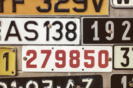 license plate: Sepia toned image of old number plates on a metal garage door
