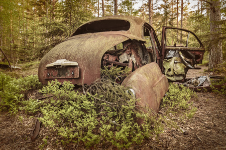 scrap car: Retro styled image of an old rusted and weathered scrap car in a forest