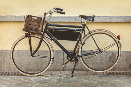 Retro styled sepia image of a vintage black transport bicycle with wooden crate
