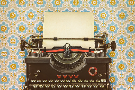 Retro styled image of an old typewriter with a blank sheet of paper in front of wallpaper with a flower print