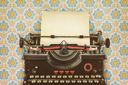 typewriter: imagen de una vieja máquina de escribir de estilo retro con una hoja de papel en blanco delante de papel tapiz con un estampado de flores Foto de archivo