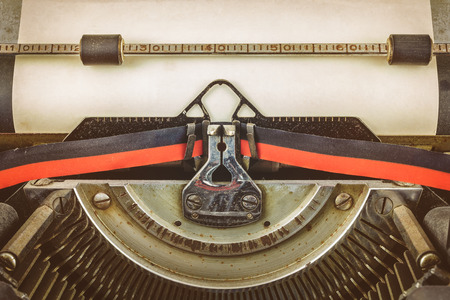 hoja en blanco: imagen de una máquina de escribir de cosecha de estilo retro con una hoja de papel en blanco Foto de archivo