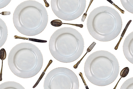 kitchenware: Pattern of vintage dinner plates, knives, forks and spoons isolated on a white background