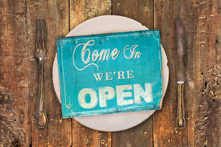 welcome symbol: Vintage open sign on a dinner plate with fork and knive on an old wooden table