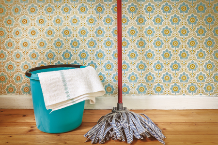 cleaning tools: Sepia toned image of a floor mop and bucket in front of retro wallpaper