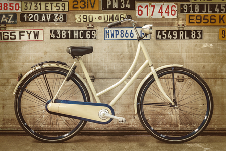 old school bike: Sepia styled image of a vintage lady bicycle in an old factory with old number plates attached to the door Stock Photo