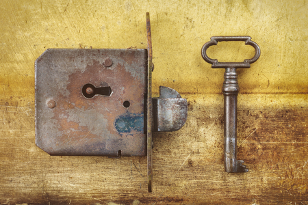 lock and key: Ancient weathered door lock with key on a metal background Stock Photo