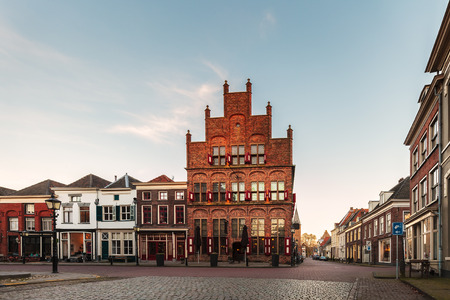 Ancient row of houses with restaurants in the historic Dutch city of Doesburg during sunset