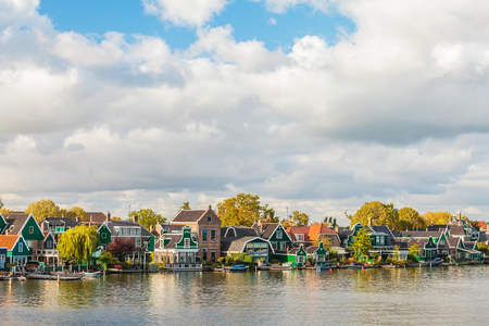 holland: Traditional green wooden Dutch historic houses at the river side in Zaandijk