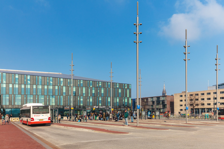 bus station: DELFT, THE NETHERLANDS - MARCH 3, 2016: Bus station with commuters in front of the train station in Delft, The Netherlands