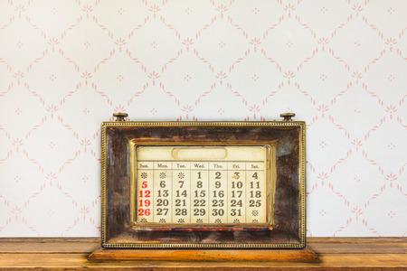Vintage calendario desktop su un tavolo di legno di fronte a retro carta da parati