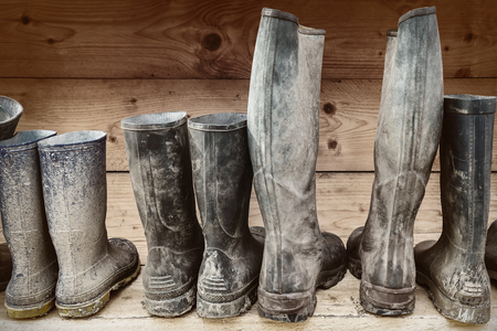 Row of muddy boots in front of a wooden wall Imagens - 56155218