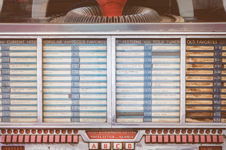 jukebox: ROSMALEN, THE NETHERLANDS - MAY 8, 2016: Retro styled image of a vintage weathered jukebox on a flee market in Rosmalen, The Netherlands