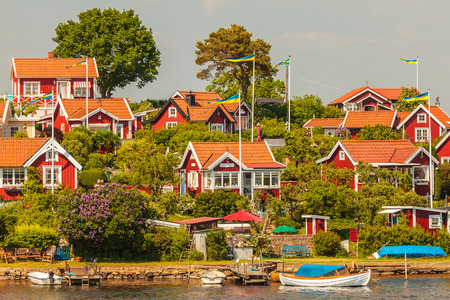 Typical red swedish wooden houses with boats in the city of Karlskrona